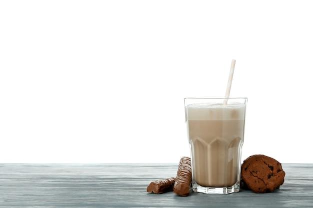 Chocolademilkshake, koekjes en chocoladestokken op houten lijst die op witte achtergrond wordt geïsoleerd