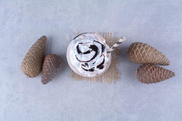 Chocolademilkshake met slagroom en dennenappel op marmeren tafel.