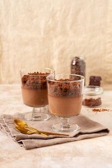 Chocolademousse met brownie in glazen potten op een lichte leisteen, steen of betonnen ondergrond. heerlijk dessert. selectieve focus
