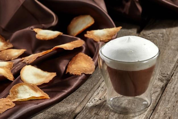 Chocolademousse met schuimige melk in glas met zoete krokante chips