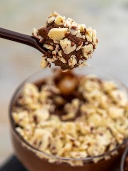 Chocolademousse op lepel met witte chocoladeschilfers.