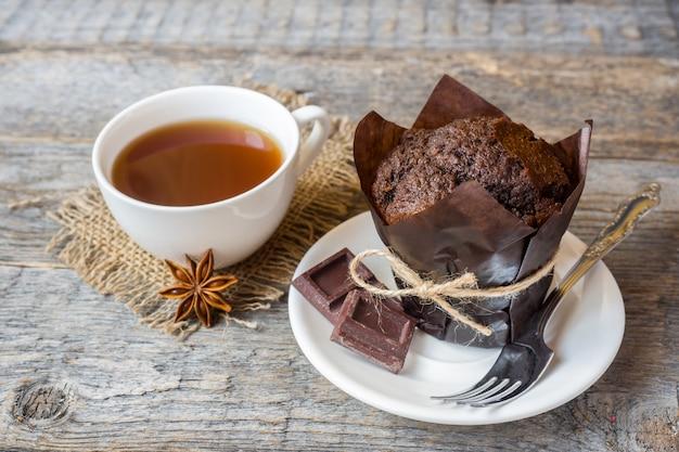 Chocolademuffin en een kop koffie op een houten oppervlak.
