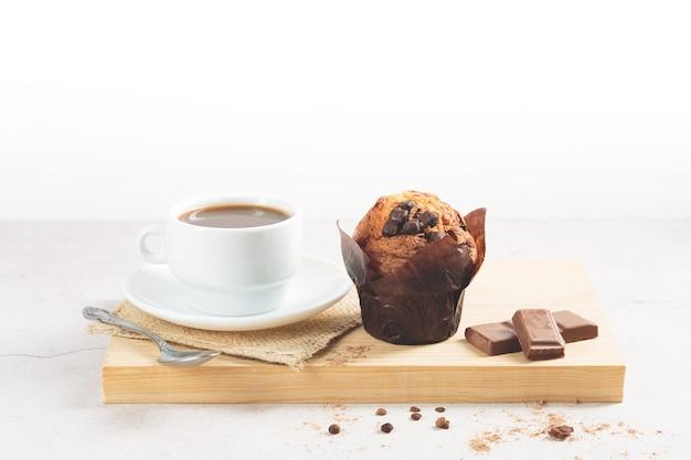 Chocolademuffin en een kopje koffie, op een houten bord op een witte achtergrond.