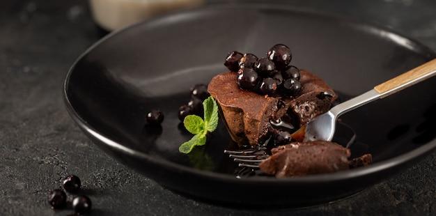 Chocolademuffin met bosbessen in zwarte plaat op donkere achtergrond met koffie