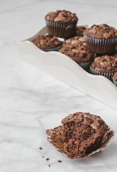 Chocolademuffins in een dienblad worden gediend dat. een daarvan is gebeten en geïsoleerd