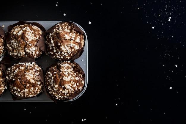 Chocolademuffins in papieren cupcake houder op bakplaat tegen zwarte achtergrond
