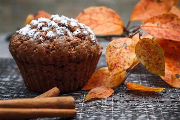 Chocolademuffins met appelvulling op een achtergrond van herfstbladeren en kaneel