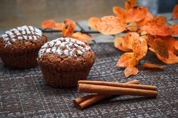 Chocolademuffins met appelvulling op een ruimte van de herfstbladeren en kaneel