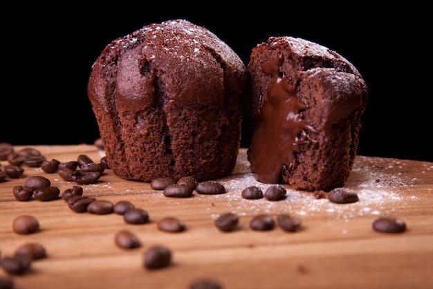 Chocolademuffins met chocolade en koffiebonen en suiker op een houten lijst en een zwarte achtergrond.