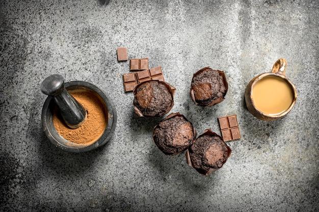 Chocolademuffins met koffie en cacao op rustieke tafel.