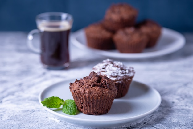 Chocolademuffins met munt op een zwarte plaat, bezaaid met poedersuiker. zelfgemaakt bakken. op de achtergrond is een kopje koffie en een bord met muffins. marmeren tafel en blauwe achtergrond.