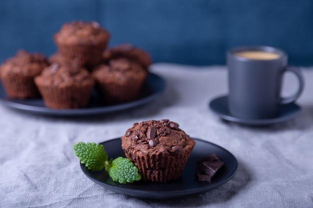 Chocolademuffins met munt op een zwarte plaat. zelfgemaakt bakken. op de achtergrond is een kopje koffie en een bord met muffins. marmeren tafel en blauwe achtergrond.