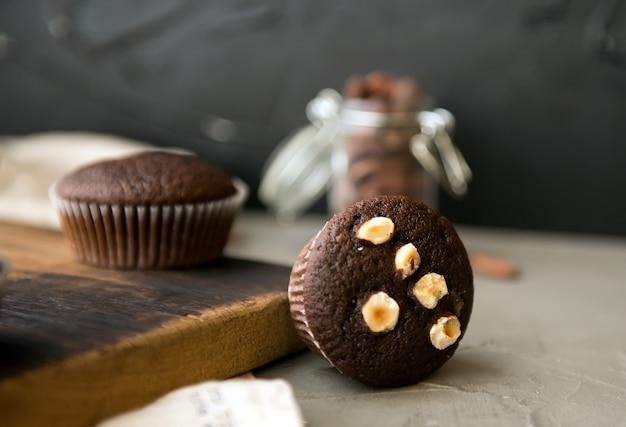 Chocolademuffins met noten op een houten tafel. heerlijk zoet dessert. rustieke stijl.