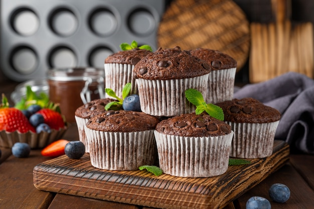 Chocolademuffins of cupcakes met chocoladedruppels met verse bessen en munt