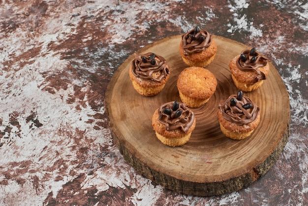 Chocolademuffins op een houten bord.