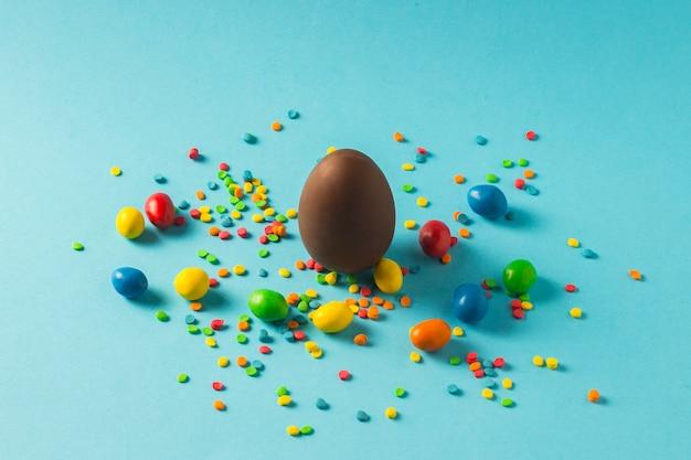 Chocoladepaasei en multi-coloured snoepjes op een blauwe achtergrond. paasviering concept.