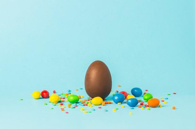 Chocoladepaasei en multi gekleurde snoepjes op een blauwe oppervlakte. paasviering concept.
