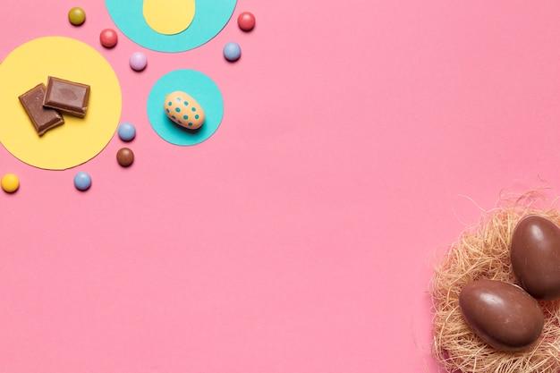 Chocoladepaaseieren en gemsuikergoed met exemplaarruimte voor het schrijven van de tekst op roze achtergrond