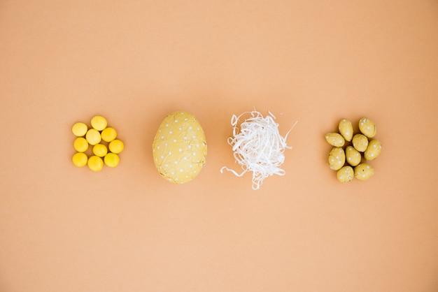 Chocoladepaaseieren met klein suikergoed op beige lijst