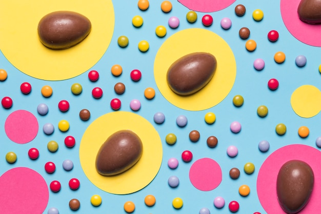 Chocoladepaaseieren op roze en geel cirkeldocument frame dat met gemssuikergoed wordt verfraaid op blauwe achtergrond