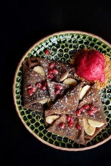 Chocoladepannekoek met bananen, granaatappel en sorbet