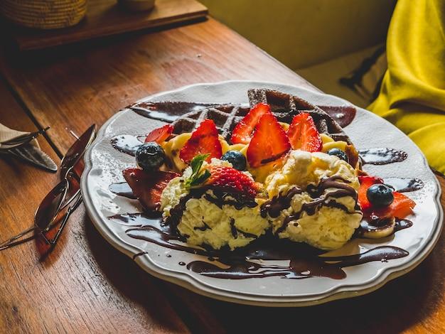 Chocoladepannekoeken met banaan, aardbei, bosbes, roomijs, brownies en chocolade.