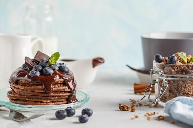 Chocoladepannekoeken met stroop en bessen, chocoladegranola en melk. ontbijtconcept, blauwe achtergrond