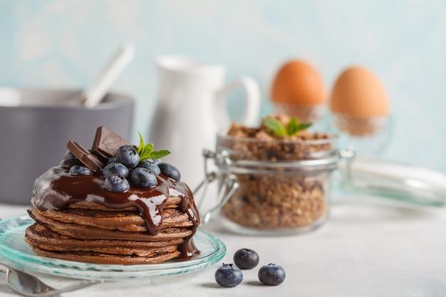 Chocoladepannekoeken met stroop en bessen, chocoladegranola, melk en eieren. ontbijtconcept, blauwe achtergrond