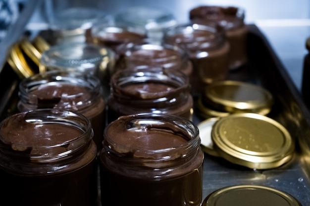 Chocoladepasta in lepel met pot op donkere achtergrond