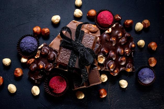 Chocoladereep, stukjes pure chocolade en noten. praliné chocoladesnoepjes.