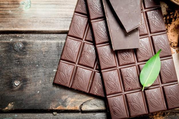 Chocoladerepen met groen blad. op een houten achtergrond.