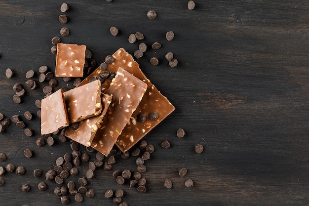 Chocoladerepen met pistache en choco druppels bovenaanzicht op een donkere achtergrond