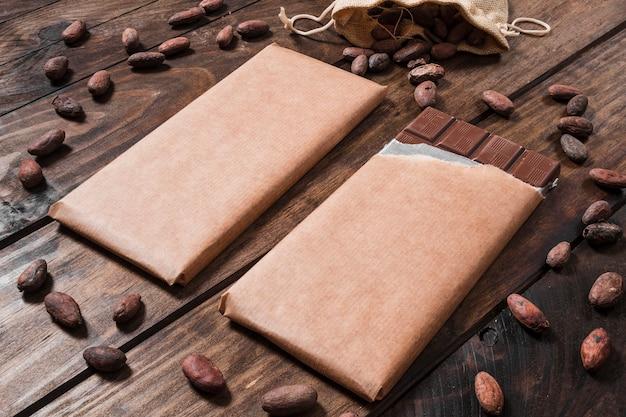 Chocoladerepen omringd met cacaobonen op houten bureau