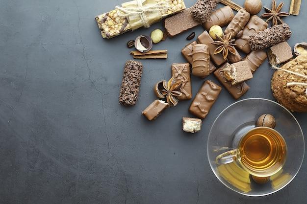 Chocoladerepen op een zwarte achtergrond in tegenlicht. chocolade met vulling. zoete snoepjes voor snack en thee.
