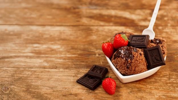 Chocoladeroomijs in een kom dessert versierd met chocolade en aardbeien