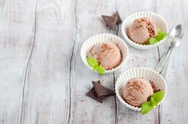 Chocoladeroomijs in witte kommen op een houten lijst.