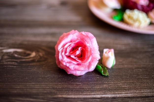 Chocoladeroze roos op een bruine houten ondergrond er is een bord met andere chocoladebloemen