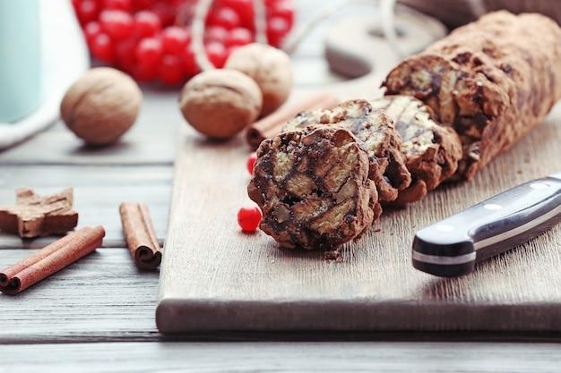 Chocoladesalami met walnoten en rode bessen op een tafel, close-up