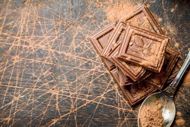 Chocoladeschijfjes met cacaopoeder. op een houten achtergrond.