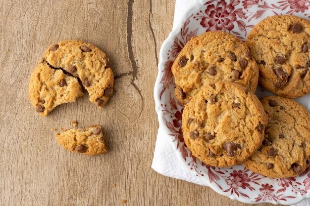 Chocoladeschilfer en vanillekoekjes op een verfraaide plaat over textiel met gebroken koekje over een houten lijst.