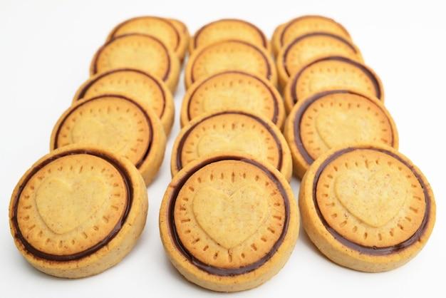 Chocoladeschilferkoekjes die op witte achtergrond worden geïsoleerd. koekjes gevuld met cacaoroom en hazelnoten.