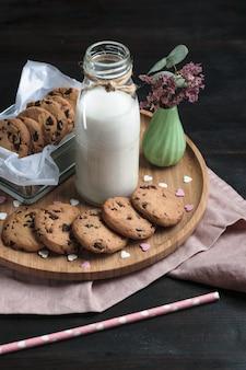 Chocoladeschilferkoekjes en een fles melk op een houten lijst.
