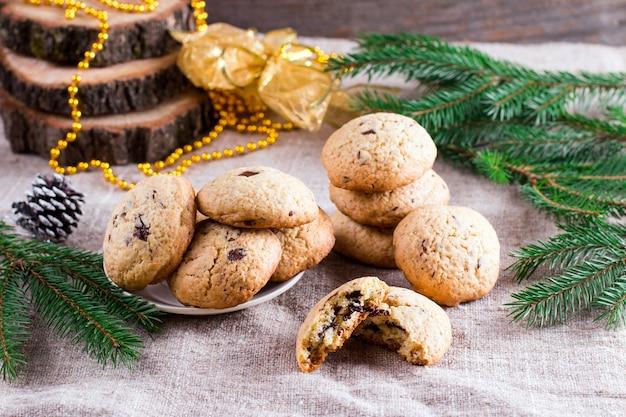 Chocoladeschilferkoekjes en kerstversiering op houten tafel