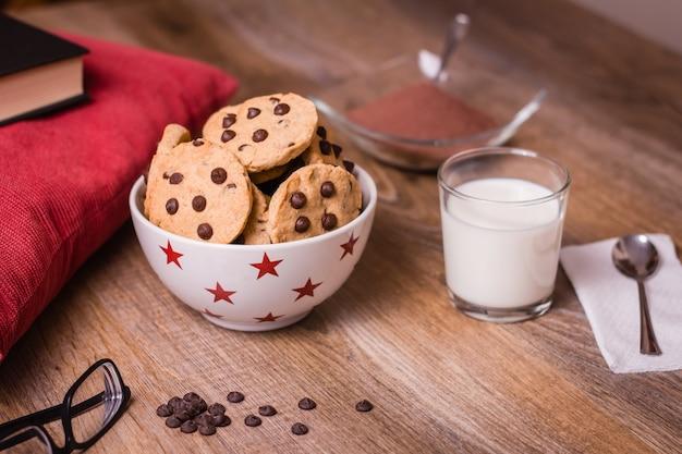Chocoladeschilferkoekjes en melk op houten achtergrond