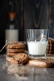 Chocoladeschilferkoekjes en melk op houten lijst