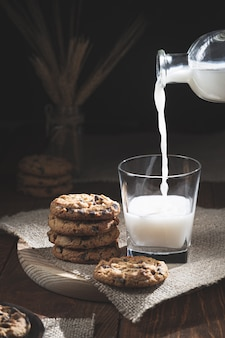 Chocoladeschilferkoekjes en melkfles die melk in een glas op een houten basis morsen