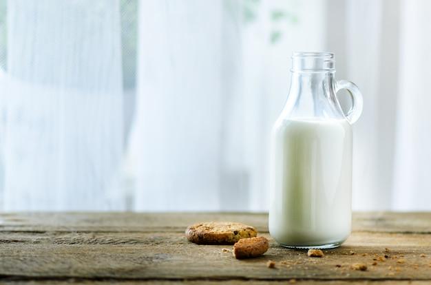 Chocoladeschilferkoekjes, fles en glas melk op houten lijst dichtbij venster. zonnige ochtend