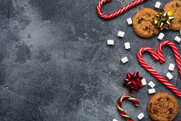 Chocoladeschilferkoekjes kerststokken karamel rood goud landschap en marshmallow op donkergrijs. copyspace frame.