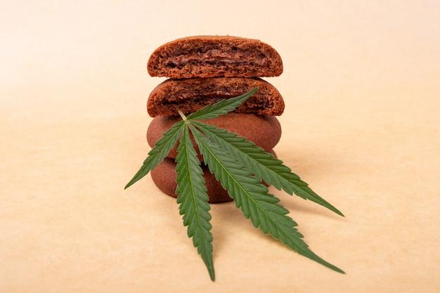 Chocoladeschilferkoekjes met groene bladmarihuanainstallatie. snoepjes met cannabis, stapel koekjes.