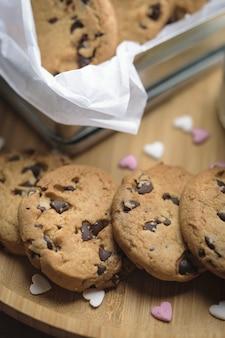 Chocoladeschilferkoekjes op een houten plaat en in een kleine doos die met suikerharten wordt gedecoreerd.